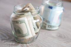Argent Dollars et euro dans des deux pots ouverts sur le fond en bois gris Copiez l'espace Photos stock