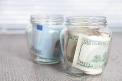 Argent Dollars et euro dans des deux pots ouverts sur le fond en bois gris Copiez l'espace Image libre de droits