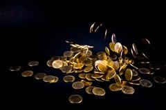 Argent en baisse de pièces d'or à l'arrière-plan foncé, concept d'affaires Photos libres de droits