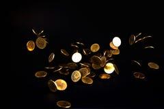 Argent en baisse de pièces d'or à l'arrière-plan foncé, concept d'affaires Image stock