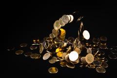 Argent en baisse de pièces d'or à l'arrière-plan foncé, concept d'affaires Photographie stock