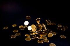 Argent en baisse de pièces d'or à l'arrière-plan foncé, concept d'affaires Images libres de droits