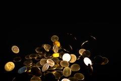 Argent en baisse de pièces d'or à l'arrière-plan foncé, concept d'affaires Images stock