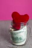 Argent et coeurs rouges Dollars dans le pot ouvert sur le fond en bois gris Copiez l'espace Amour Jour de Valentine Photos stock