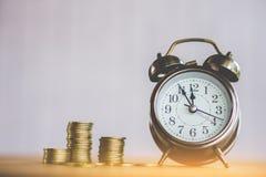 Argent et concept de temps avec la pile de la pièce de monnaie et de l'horloge sur la table photos libres de droits