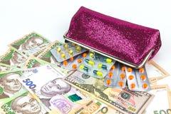 Argent et pilules : un symbole du coût croissant de médecines dans le monde et en Ukraine photos stock