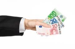 Argent et sujet d'affaires : la main dans un costume noir tenant les billets de banque 10,20 et l'euro 100 sur le blanc a isolé l Images stock