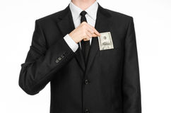 Argent et thème d'affaires : un homme dans un costume noir tenant une facture de 100 dollars et comporte un geste de main sur un  Images stock