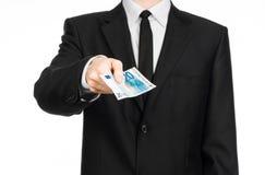 Argent et thème d'affaires : un homme dans un costume noir tenant une facture de 20 euros et expositions un geste de main sur un  Photos stock