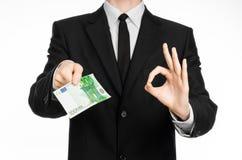 Argent et thème d'affaires : un homme dans un costume noir tenant une facture de 100 euros et expositions un geste de main sur un Images stock
