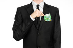 Argent et thème d'affaires : un homme dans un costume noir tenant une facture de 100 euros et expositions un geste de main sur un Image libre de droits