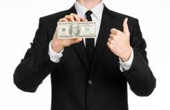 Argent et thème d'affaires : un homme dans un costume noir tenant une facture de 100 dollars et comporte un geste de main sur un  Images libres de droits