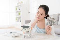 Argent liquide de billet de banque de l'épargne de compte de participation de femme au foyer Photographie stock libre de droits