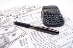 Argent liquide et calculatrice de feuille d'impôt  images stock