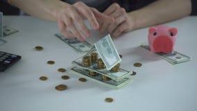 Argent plié comme maison, symbole de stabilité financière, l'épargne pour acheter le logement banque de vidéos