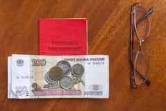 Argent, points et certificat de pension sur une surface-traduction en bois dans le Russe : certificat du ` s de retraité Photos libres de droits