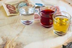 Argent pour une boisson sur une table en bois à l'arrière-plan, dans le premier plan par verre avec de l'alcool coloré Photographie stock libre de droits
