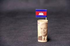 Argent roulé de billet de banque cinq mille Riel et bâtons cambodgiens avec le mini plancher et fond gris-foncé du drapeau 0n du  photographie stock libre de droits