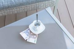Argent thaïlandais et tasse de café vide sur une table en verre de café extérieur Paiement, astuce photo stock