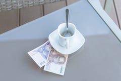 Argent thaïlandais et tasse de café vide sur une table en verre de café extérieur Paiement, astuce photos stock