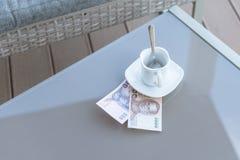 Argent thaïlandais et tasse de café vide sur une table en verre de café extérieur Paiement, astuce photo libre de droits