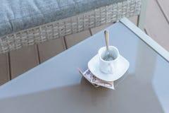 Argent thaïlandais et tasse de café vide sur une table en verre de café extérieur Paiement, astuce photographie stock libre de droits