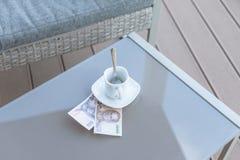 Argent thaïlandais et tasse de café vide sur une table en verre de café extérieur Paiement, astuce image stock
