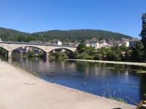 Argentat bridge over the river. Argentat bridge in the sun over the blue Dordogne river royalty free illustration