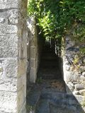 Argentat passageway near the river. Argentat stone passageway between houses near the Dordogne river with green vines Stock Photo