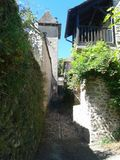 Argentat passageway near the river. Argentat stone passageway between houses near the Dordogne river with green vines Stock Image