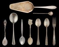 Argenteria d'annata, cucchiai antichi, coltelli, pale del dolce isolate su fondo nero isolato Argenteria antica retro immagini stock
