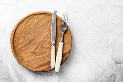 Argenteria d'annata e piatto di legno su fondo concreto grigio Fotografia Stock Libera da Diritti