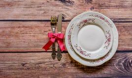 Argenteria d'annata legata con l'arco e la lombata rosa su di legno rustico Immagine Stock