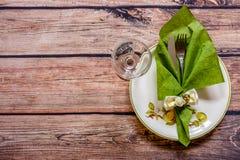 Argenteria d'annata su un tovagliolo verde su un piatto e su un bicchiere di vino sopra Fotografia Stock