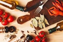 Argenterie sur le conseil avec des épices, des tomates-cerises et des cancers photographie stock