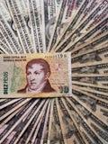 Argentijns bankbiljet van tien peso's en achtergrond met Amerikaanse dollarsrekeningen