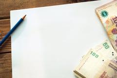 Argentijns geld, peso's op de lijst met een witte, lege kaart en een potlood stock foto's