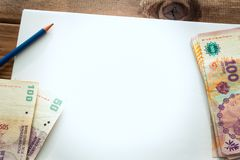 Argentijns geld, peso's op de lijst met een witte, lege kaart en een potlood royalty-vrije stock foto