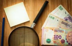 Argentijns geld, peso's op de lijst met een witte lege kaart, een vergrootglas en een potlood royalty-vrije stock afbeeldingen