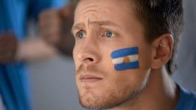 Argentijns voetbalventilator het letten op voetbalspel op TV, hoop van overwinning, close-up royalty-vrije stock afbeeldingen
