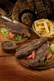 Argentina Beef. Two Roast meat (Asado and Vacío) with french frites and vegetables, Knife (facón), horseshoe, and whip Stock Photos