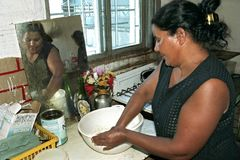 Cooking Argentinian woman in shabby kitchen. ARGENTINA, Buenos Aires province, city Lanus: Portrait of an Argentine woman during cooking, baking with flour and Royalty Free Stock Photo