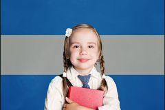 Argentina concept with little girl student with book against the Argentinean flag background.  stock photography
