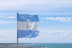 Argentina flag with atlantic ocean in background. Argentina landscape royalty free stock photo