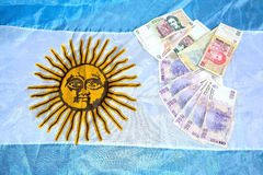 Argentina flag and cash. Argentina flag light blue white gold sun travel living country currency cash money finance economy paper coin stock images