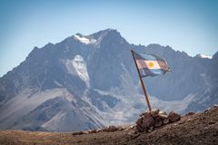 Argentina flag with Cerro Tolosa Mountain on background in Cordillera de Los Andes - Mendoza Province, Argentina. Argentina flag with Cerro Tolosa Mountain on royalty free stock photo
