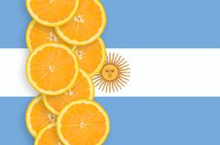 Argentina flag and citrus fruit slices vertical row. Argentina flag and vertical row of orange citrus fruit slices. Concept of growing as well as import and stock image
