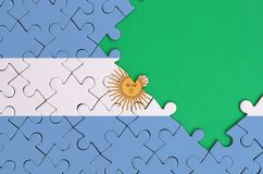 Argentina flag is depicted on a completed jigsaw puzzle with free green copy space on the right side.  royalty free illustration
