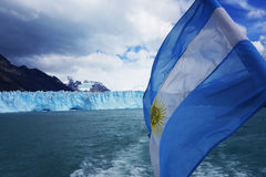 Argentina Flag in front of the Perito Moreno Glacier. Patagonia, Argentina royalty free stock photos