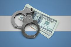 Argentina flag with handcuffs and a bundle of dollars. Currency corruption in the country. Financial crimes.  royalty free stock images